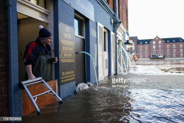 Man looks out over the flood defences at a business premises as the River Ouse in York floods as rain and recent melting snow raise river levels on...