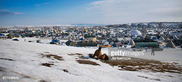 A man looks out over the Oceti Sakowin Camp on the edge of the Standing Rock Sioux Reservation on December 3 2016 outside Cannon Ball North Dakota as...