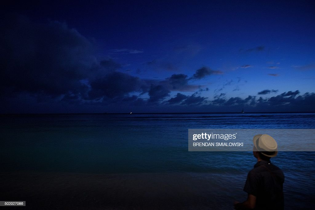 A man looks out over Waikiki Bay during dusk December 19, 2015 in Honolulu, Hawaii. US President Barack Obama and the First Family are in Hawaii on vacation.