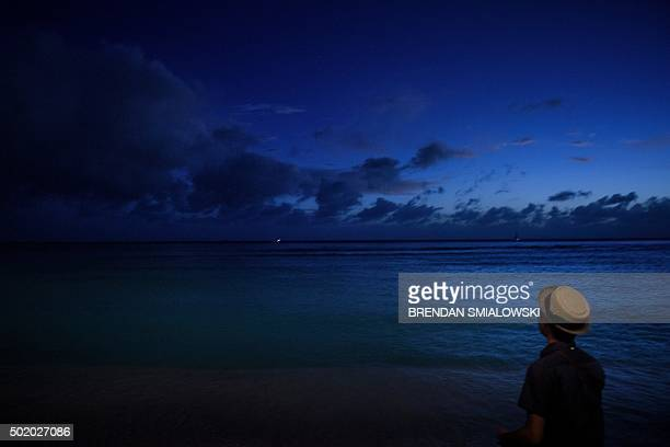 A man looks out over Waikiki Bay during dusk December 19 2015 in Honolulu Hawaii US President Barack Obama and the First Family are in Hawaii on...