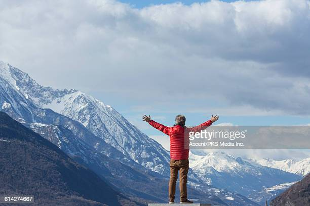Man looks out to mountains and village, arms out