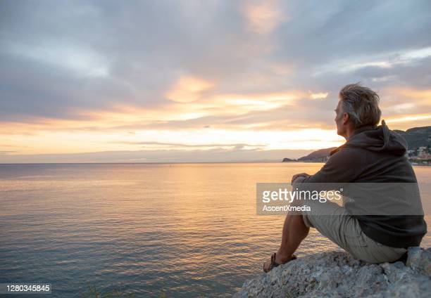 man looks out to sea from coastal area at sunrise - sunrise contemplation stock pictures, royalty-free photos & images