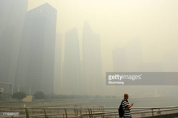 Man looks out towards the city skyline from the boardwalk at Marina Bay as buildings in the central business district stand shrouded in smog in...