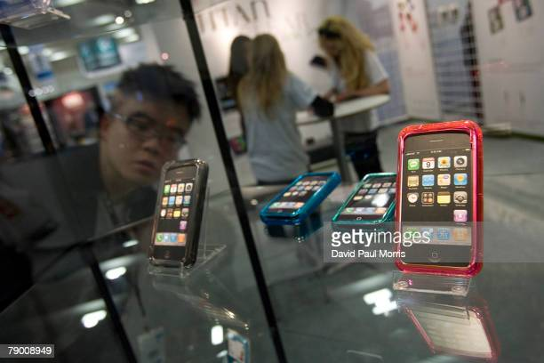 A man looks over a case of iPhones at the 2008 Macworld conference and expo at the Moscone Center January 15 2008 in San Francisco California The...
