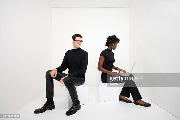 Man looks over at woman using laptop