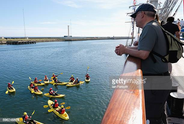 A man looks overboard from one of the ships as kayakers paddle alongside during the North Sea Tall Ships Regatta on August 27 2016 in Blyth England...