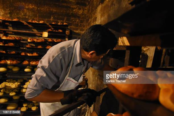 A man looks taking out bread of the dead from a woodburning oven as part of the Pan de Muerto manufacturing on October 30 2018 in Mexico City Mexico...
