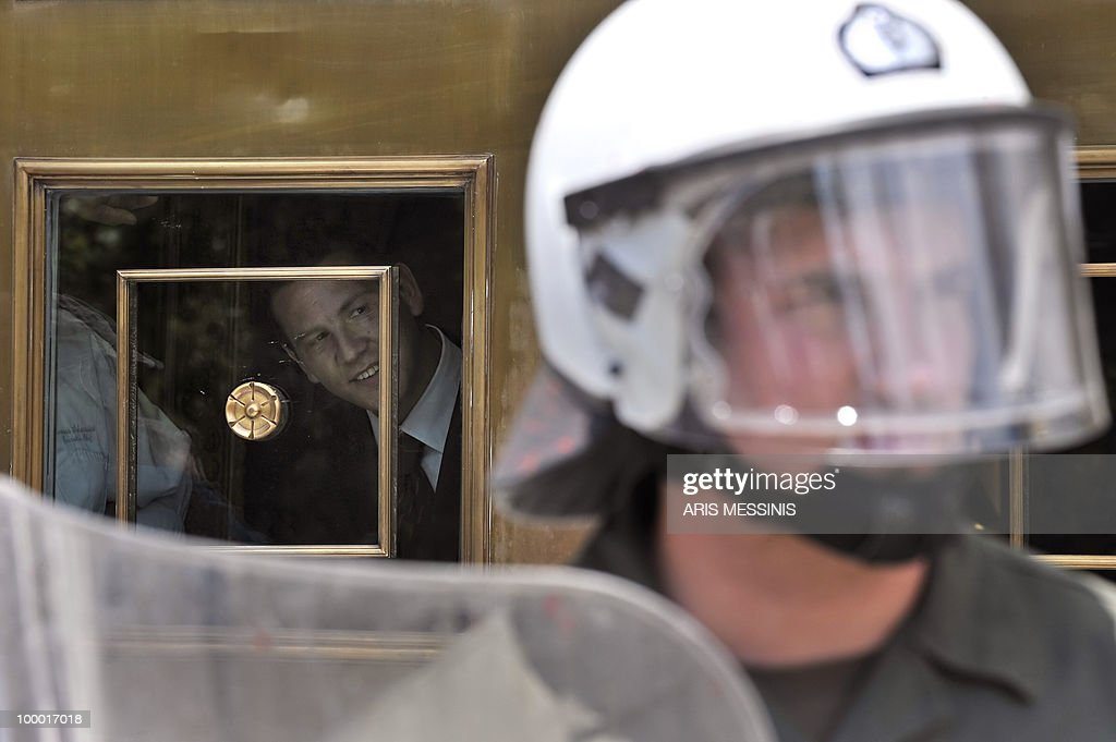 A man looks through a door of a luxury hotel during a protest marking the 24-hour general strike against the austerity measures in central Athens on May 20, 2010. Thousands of protesters took to the streets of Athens and second city Thessaloniki in a new general strike against the government's debt-dictated austerity spending cuts and pension reforma protest during a 24-hours general strike on May 20, 2010.