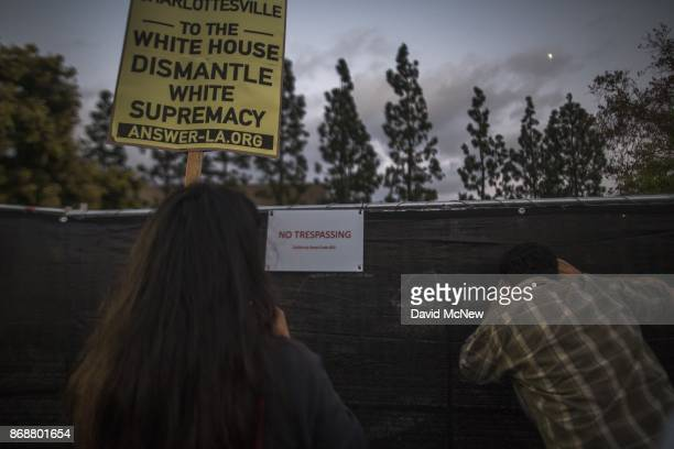 A man looks through a fence erected to keep protesters away from the site of a speaking appearance by Conservative provocateur Milo Yiannopoulos...