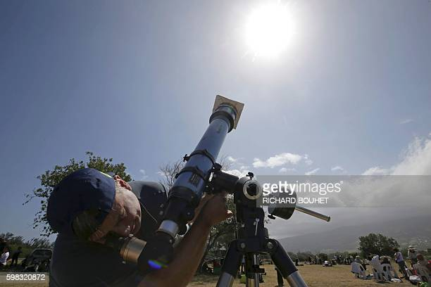A man looks through a telescope an annular solar eclipse on September 1 in SaintLouis on the Indian Ocean island of La Reunion Stargazers in south...