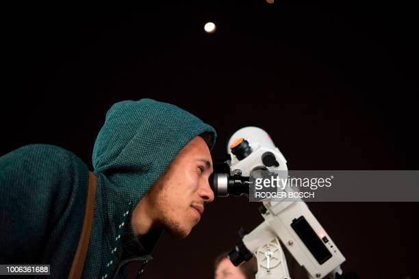 A man looks through a telescope at the full moon during a 'blood moon' eclipse in from Cape Town on July 27 2018 The longest 'blood moon' eclipse...