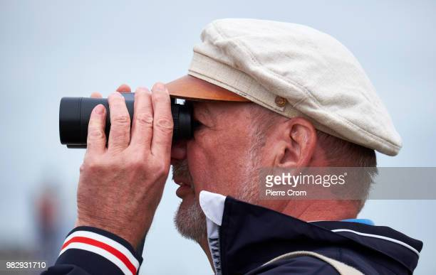 A man looks through binoculars as thousands gather at The Hague beach for the end of the Ocean Race on June 24 2018 in The Hague Netherlands