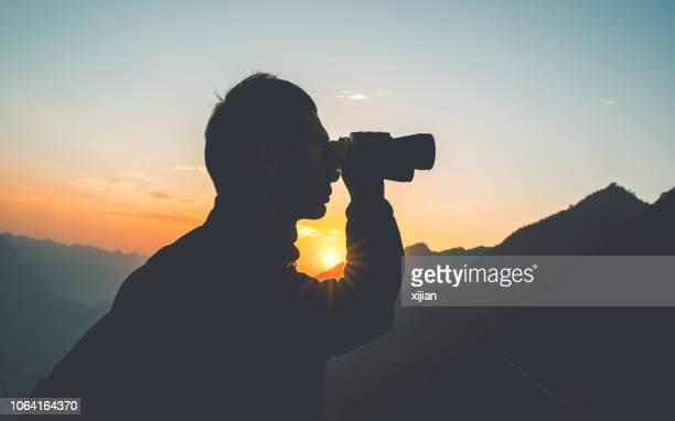 man kijkt door een verrekijker in bergen - verrekijker stockfoto's en -beelden
