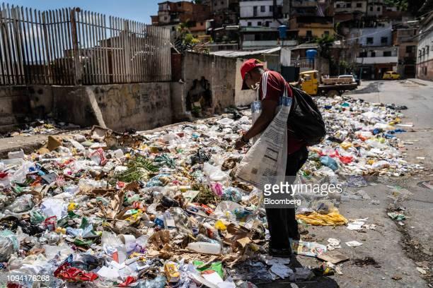 A man looks through garbage in the El Valle neighborhood of Caracas Venezuela on Monday Feb 4 2019 Residents of the poorest Caracas neighborhoods are...