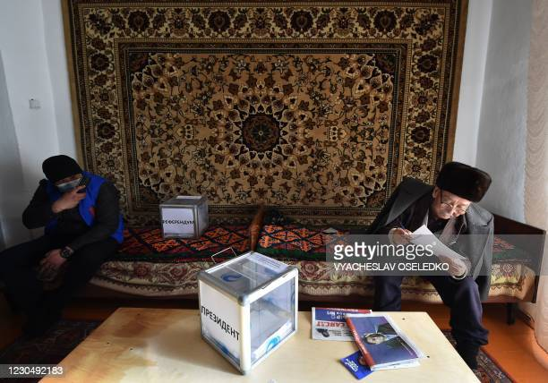 Man looks through his ballot during early voting on the eve of the main day of Kyrgyzstan's presidential election in the village of Arashan some 20...