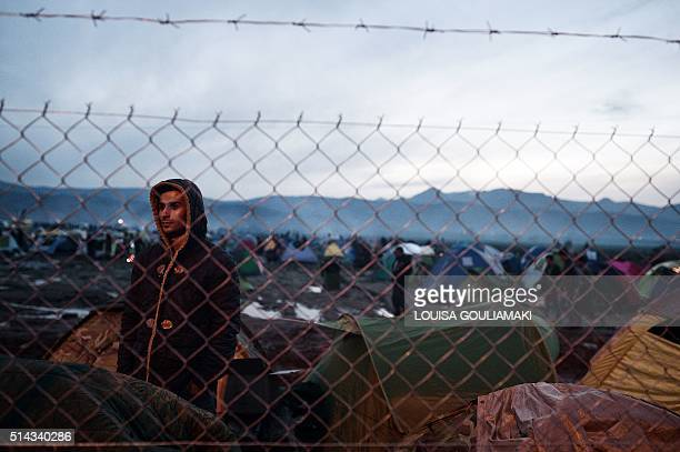 Man looks through the barbed wire fence, from the makeshift camp of the Greek-Macedonian border, near the village of Idomeni, on March 8 where...