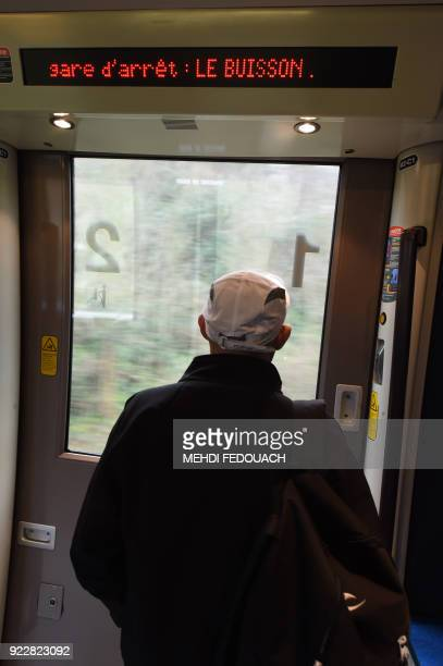 A man looks through the windo of a local TER train near Le Buisson de Cadouin train station on February 20 as the line which serves the station is...