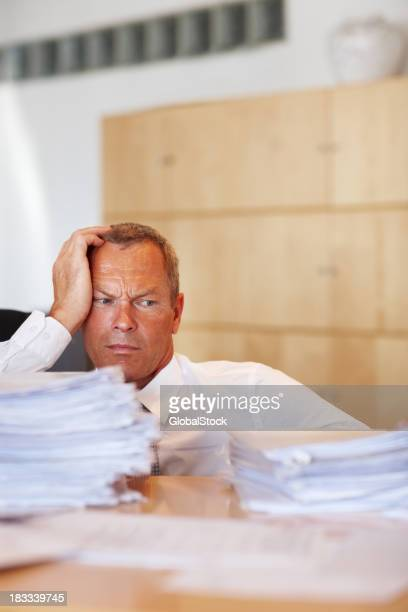 Man looks to be defeated by piles of paperwork