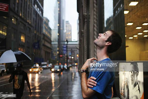 A man looks to the sky during a rainstorm in Midtown Manhattan on July 15 2014 in New York City A torrential rainstorm poared down adding to an...