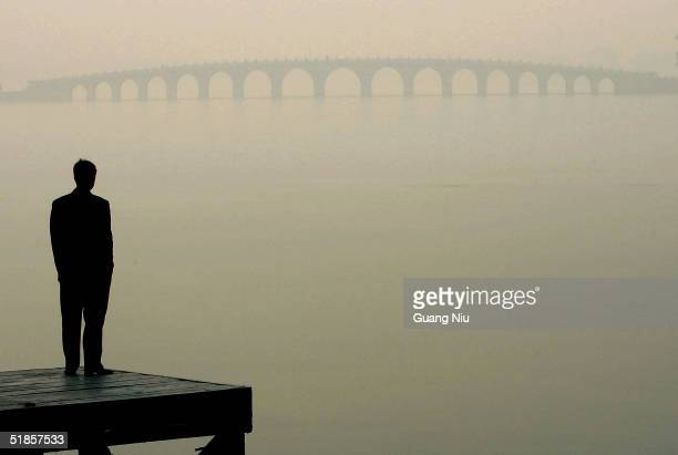 A man looks towards a bridge in heavy fog on December 14 2004 in Beijing China The bad weather has made it harder for Beijing to achieve the target...