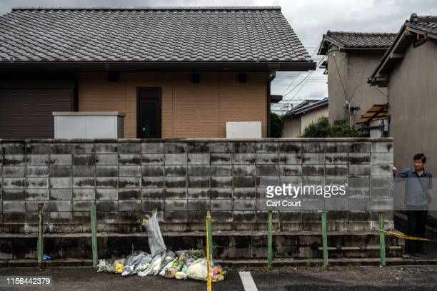 A man looks towards flowers and tributes laid near the Kyoto Animation Co studio building after an arson attack on July 19 2019 in Kyoto Japan Thirty...