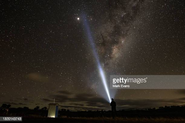 Man looks towards the supermoon and the milky way on May 26, 2021 in Rylstone, Australia. It is the first total lunar eclipse in more than two years,...