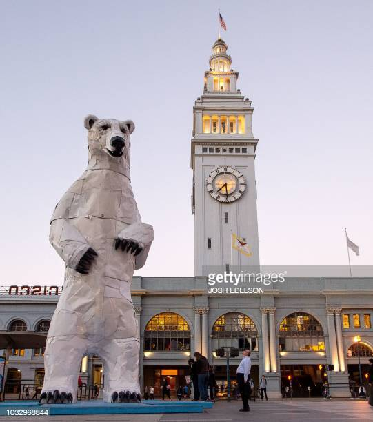 A man looks up at a polar bear statue made out of car hoods is seen in front of the Ferry Building during the Global Climate Action Summit in San...