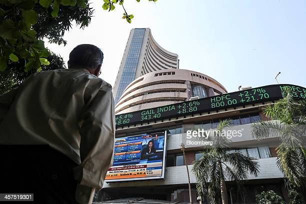 A man looks up at an electronic ticker board that indicates stock figures for GAIL India Ltd from left Housing Development Finance Corp and HDFC Bank...