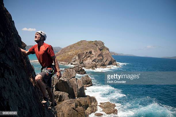 A man looks up while traditionally climbing a new route along a remote cay in the US Virgin Islands.