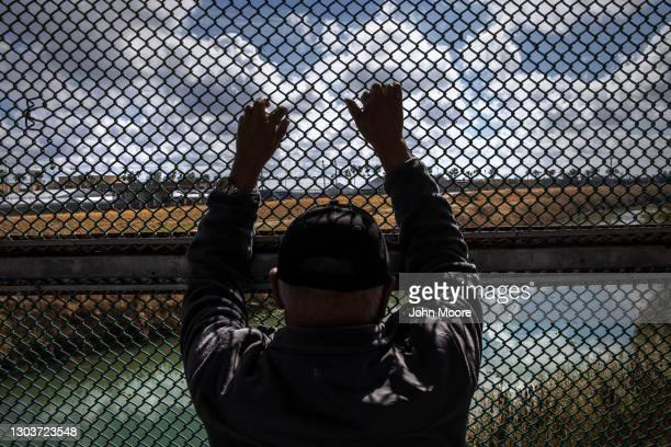 Man looks upon the Rio Grande while waiting to show his immigration documents to U.S. Immigration officers at the U.S.-Mexico border crossing on...