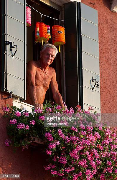 A man looks watches the opening of the votive bridge from a window for the Redentore Celebrations on July 20 2013 in Venice Italy Redentore is one of...