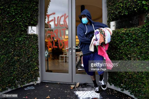 Man loots items from a Beverly Hills clothing store during demonstrations following the death of George Floyd on May 30, 2020 in Los Angeles,...