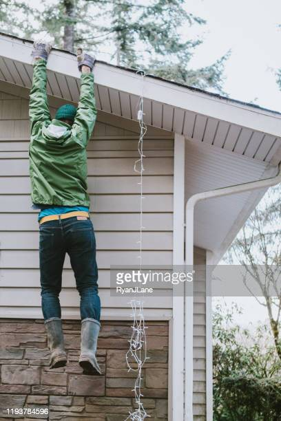 man loses ladder while hanging christmas lights on house - hanging stock pictures, royalty-free photos & images