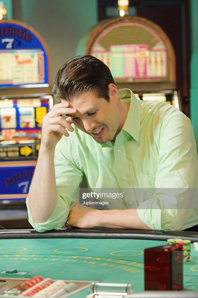 Man losing at gambling table : Stock Photo
