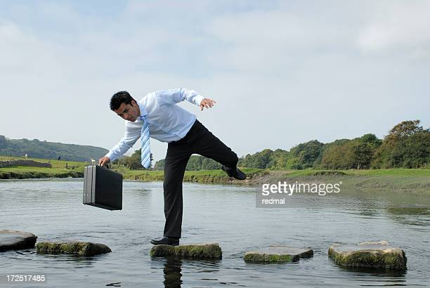 Man losing his balance on a rock near a pond