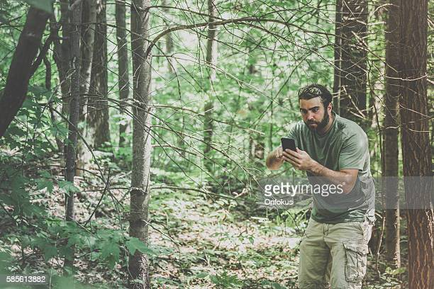 Man Lost In Forest at Sunset and Using Smartphone