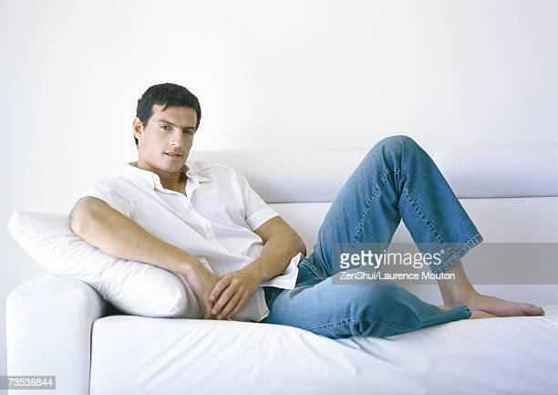 man lounging on sofa - lying down ストックフォトと画像