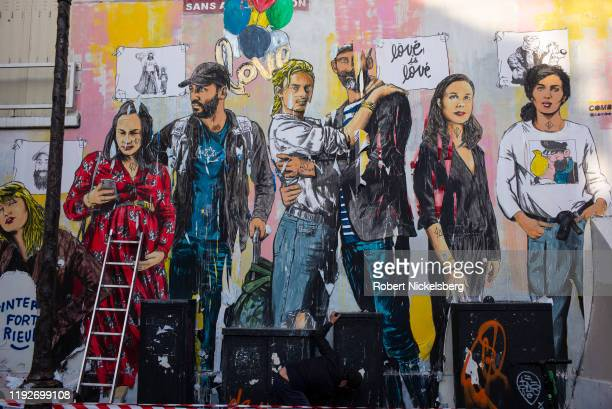 Man, lower right, cleans off paper and graffiti on a wall used by local artists in Paris, France, November 8, 2019.