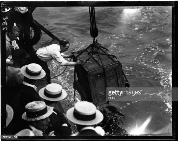 A man lowers a wooden box which contains Hungarianborn American magician escape artist and psychic debunker Harry Houdini into the East River as part...