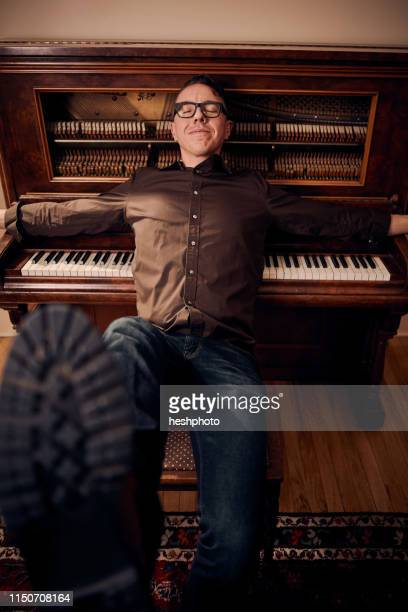 man lying against piano with eyes closed - heshphoto fotografías e imágenes de stock
