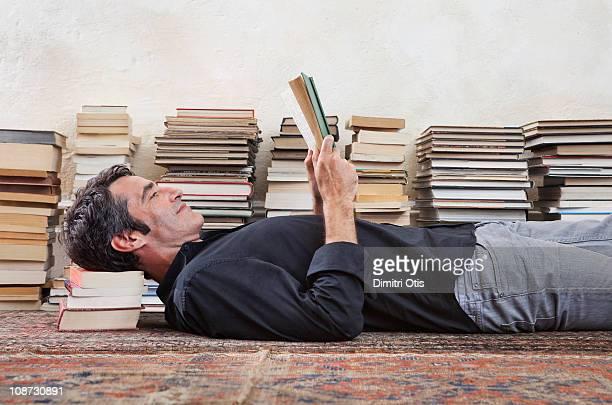Man lying amongst books, reading