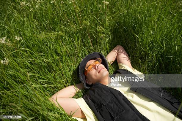 man lying back in long grass enjoying the sunshine - headwear stock pictures, royalty-free photos & images
