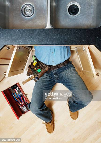 Man lying beneath sink, making repair, low section, overhead view
