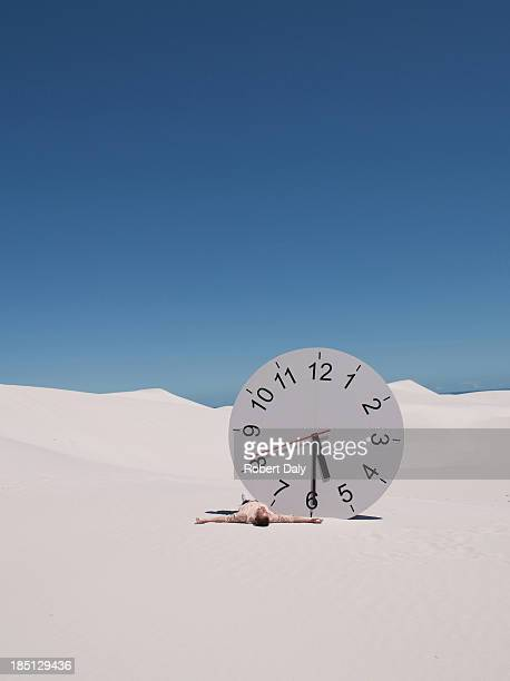 A man lying by a clock in the desert