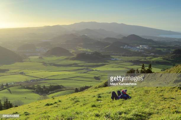 Man lying down at a green meadow, Azores