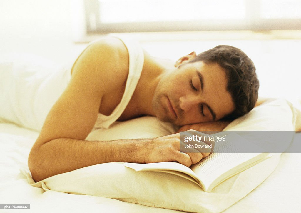Man lying down in bed with hand on book : Stock Photo