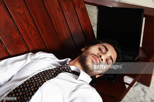 Man lying down on a sofa with laptop under head