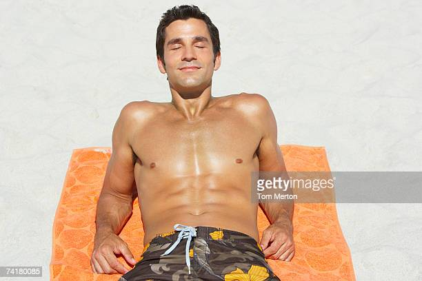 Man lying down on beach towel in sand