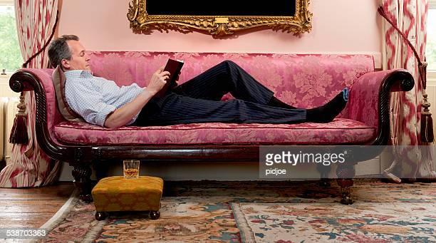 man lying down on sofa reading a book