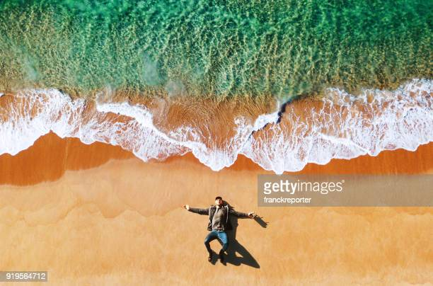 man lying down on the beach - drone point of view stock pictures, royalty-free photos & images